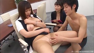 Two lovely Asian chicks take turns at playing with a stiff dick